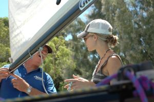 Sailors discussing set up of Hobie 16 mainsail